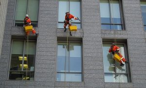 Abseiling crew at work window cleaning
